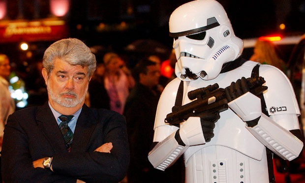 George Lucs standing next to a someone in a full black and white Stormtrooper outfit holding a gun