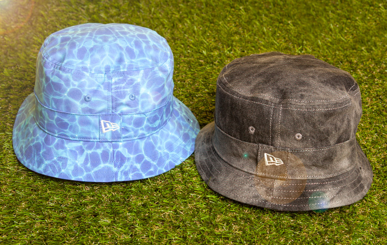 unisex new era bucket hats in blue fabric with water print and black distressed fabric sitting on grass