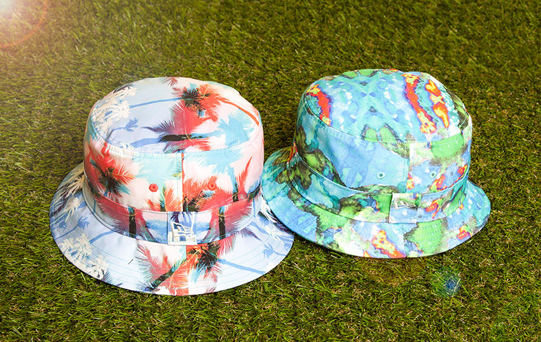 new era fabric miami vibe bucket hat and smudge bucket hat in multi colour and sitting on green grass