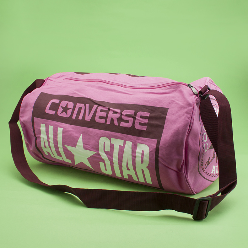 pink fabric legacy duffel bag from Converse with tonal and white branding on green background at schuh
