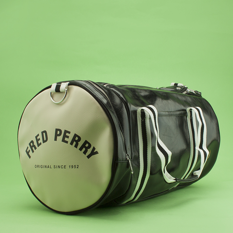black and white man-made Fred Perry barrel bag on green background from schuh