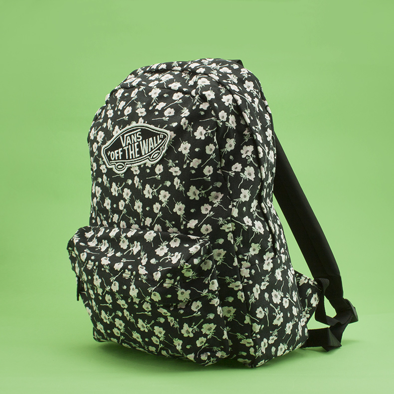 black and white floral printed Vans Realm Backpack on green background at schuh