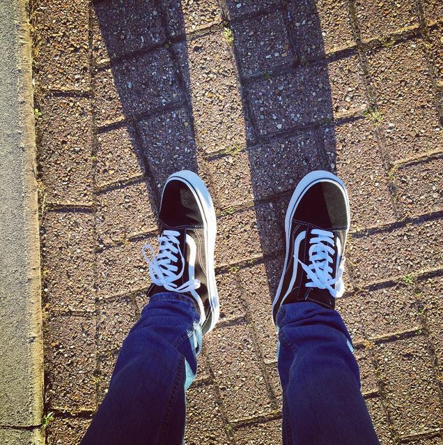 man wearing black and white vans old skool