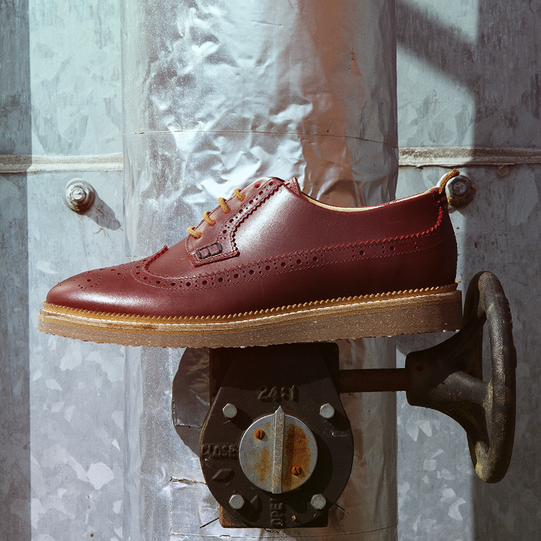 northern cobbler powen brogue shoes in burgundy leather for men with tan sole balanced on machinery
