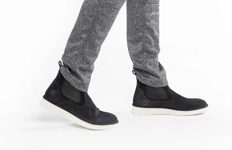 publish and timberland collaboration with male model wearing the mens chelsea boots in black suede with slim fit grey trousers