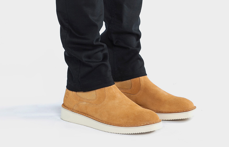 publish and timberland collaboration featuring male model with black tapered trousers wearing chelsea boots in wheat suede