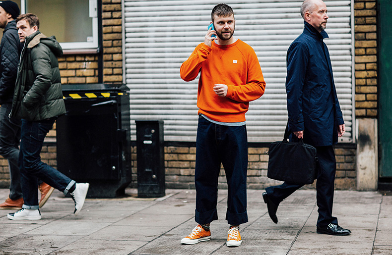 man wearing converse all star lo with orange jumper