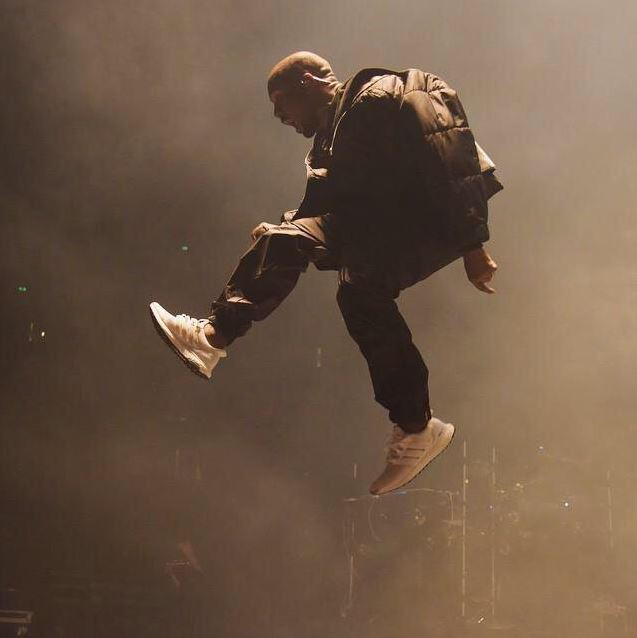 kanye west wearing triple white adidas ultra boost trainers on stage