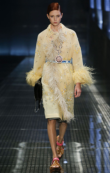 Model wearing outfit with feather detailing
