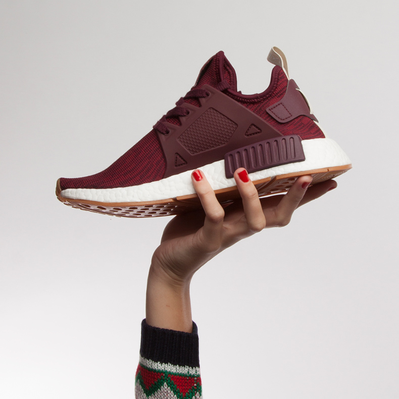 Hand holding adidas NMD's in red primeknit