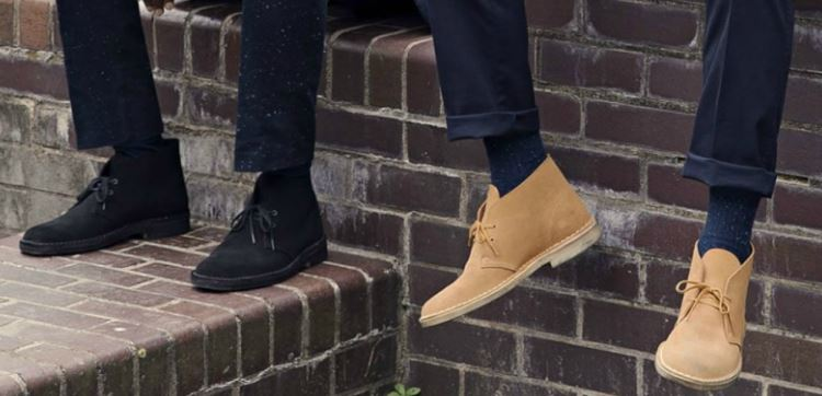 mens sitting on wall wearing desert boots