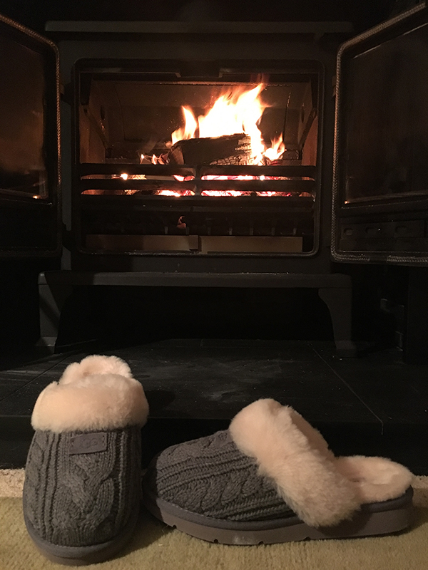 UGG Cozy Knit Grey Slippers by the fireplace