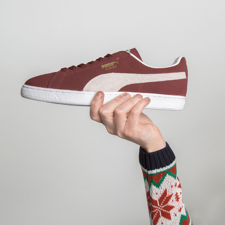 Handing wearing christmas jumper holding PUMA suede trainer