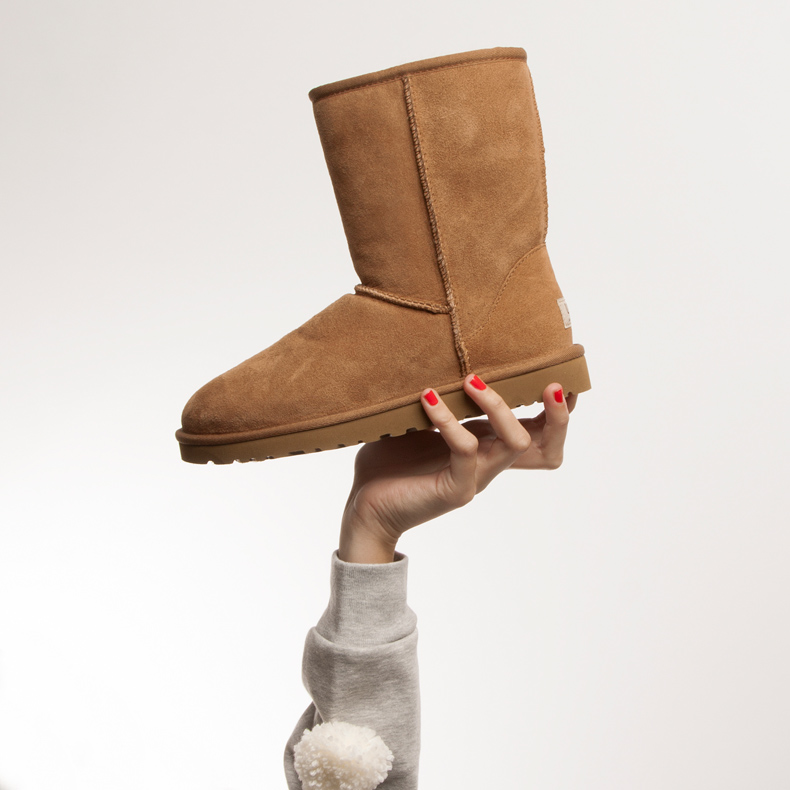 Hand holding an UGG Classic II in tan