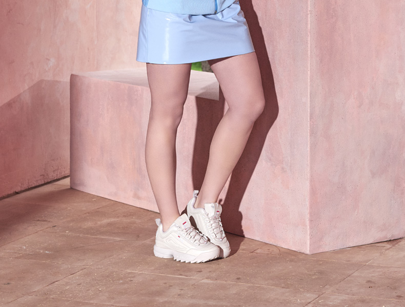 Model wearing Fila Disruptor trainers in white