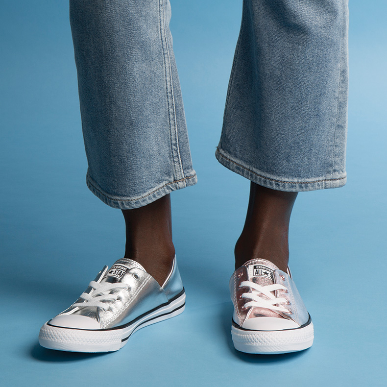 Model wearing one silver and one bronze converse coral