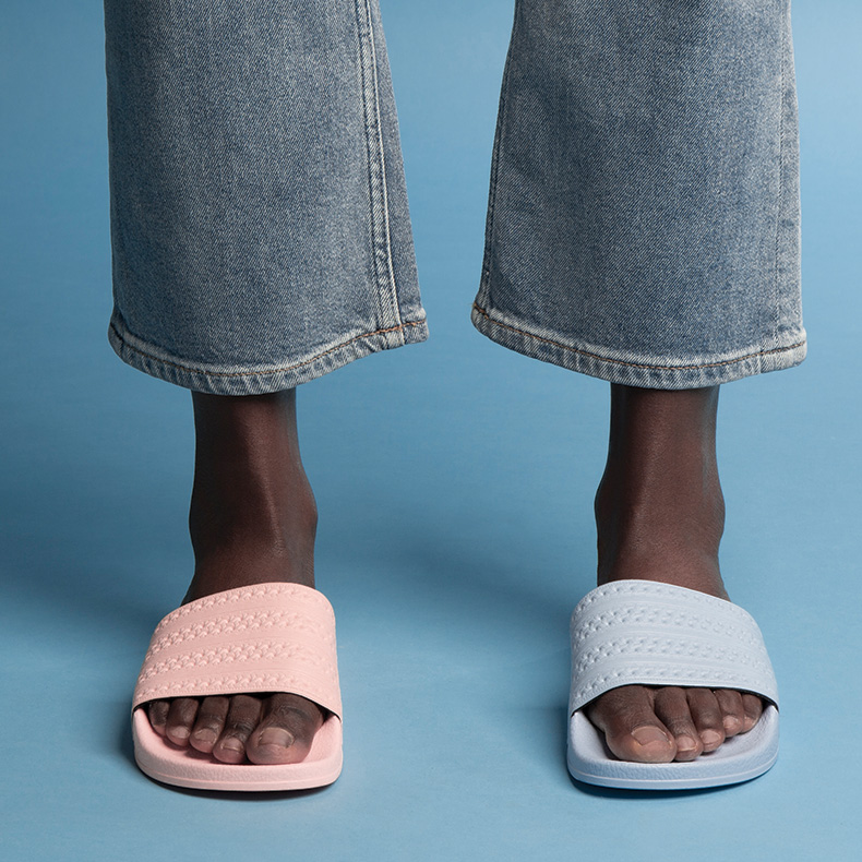 model wearing adilette slides with one pink and one blue